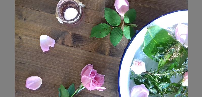 Bacile bianco con fiori e piante su una base di legno dove è adagiata una rosa e una candela accesa.