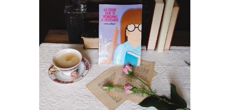 """Copia del libro """"Le cose che ti venogno a cercare"""" accanto a una tazza di caffè, fogli sparsi e delle rose adagiate su un tavolo."""