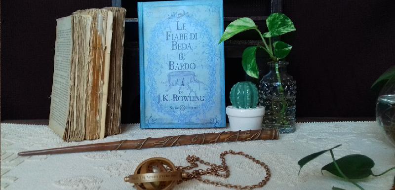 """Libro """"Le fiabe di Beda il bardo"""", la bacchetta di Hermione, una giratempo e vasetti di piante con foglie verdi."""